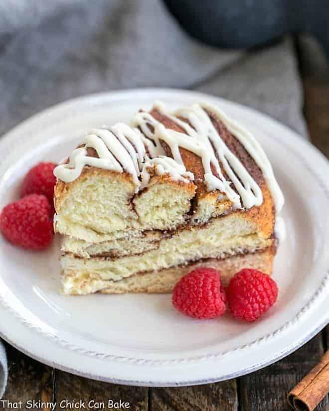 Cinnamon Twist Bread  slice on a white plate with raspberries