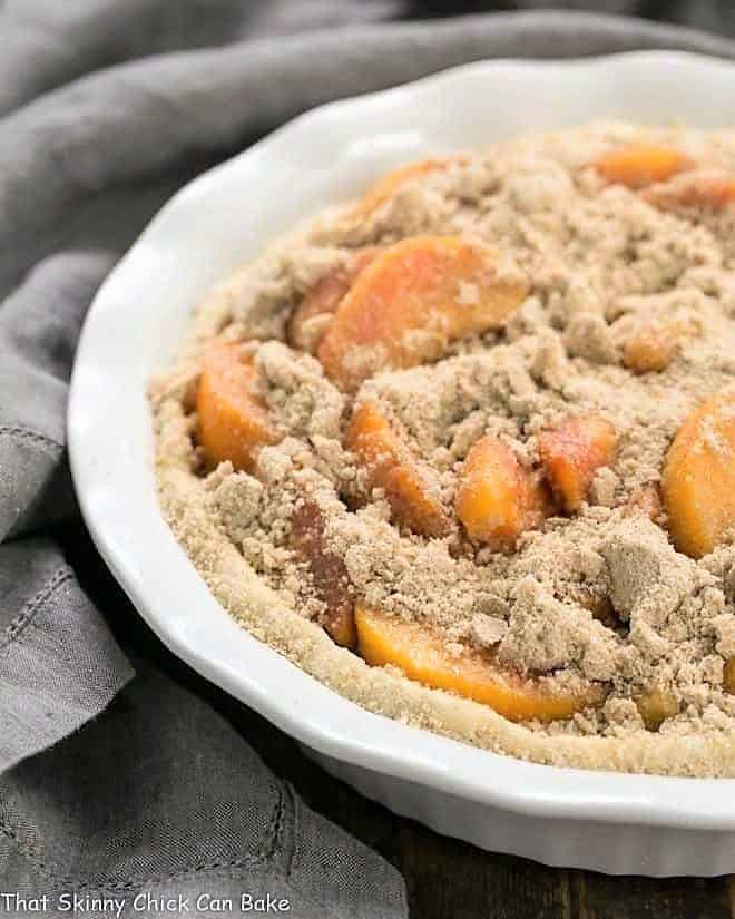Easy Peach Crumb Pie unbaked in a white pie plate