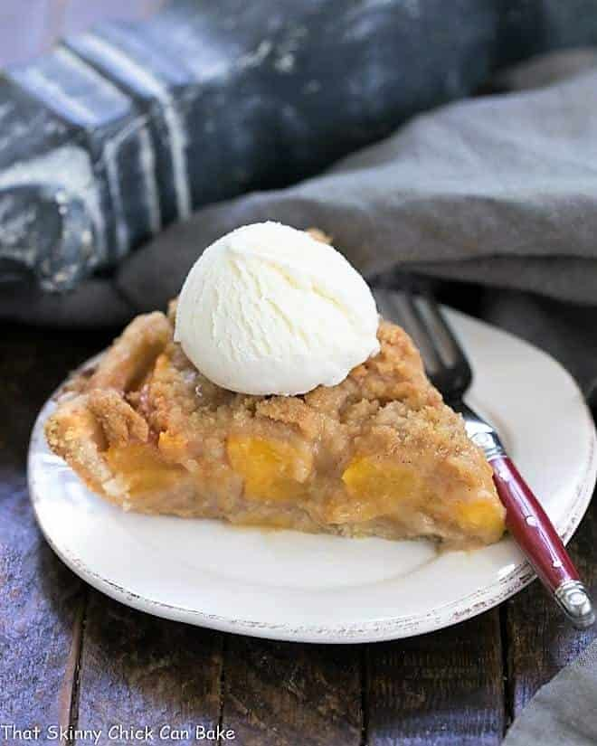 Slice of Easy Peach Crumb Pie topped with ice cream on a round white plate