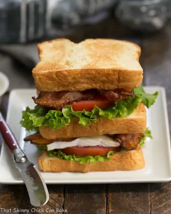 A double decker Brie Bacon Lettuce and Tomato Sandwich on a square white plate with a small red handled knife