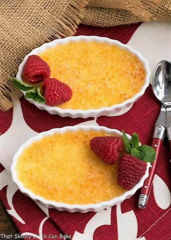 Two Classic Crème Brûlée with red handled spoons