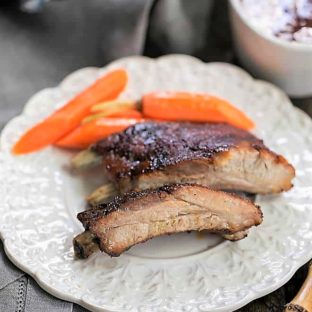 Instant Pot Baby Back Ribs on a white plate with carrots