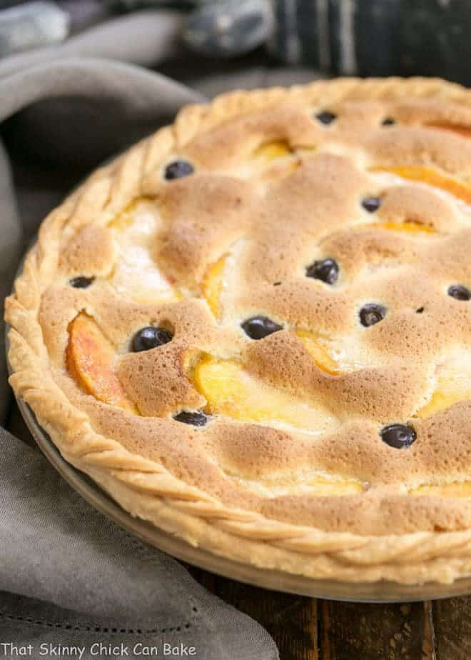Peach Blueberry Custard Pie in a glass pie dish with a braided crust