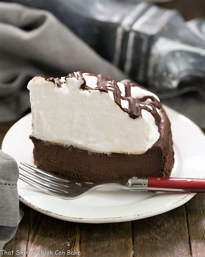 A slice of Flourless Chocolate Cake with Marshmallow Frosting on a white ceramic plate with a red handled fork