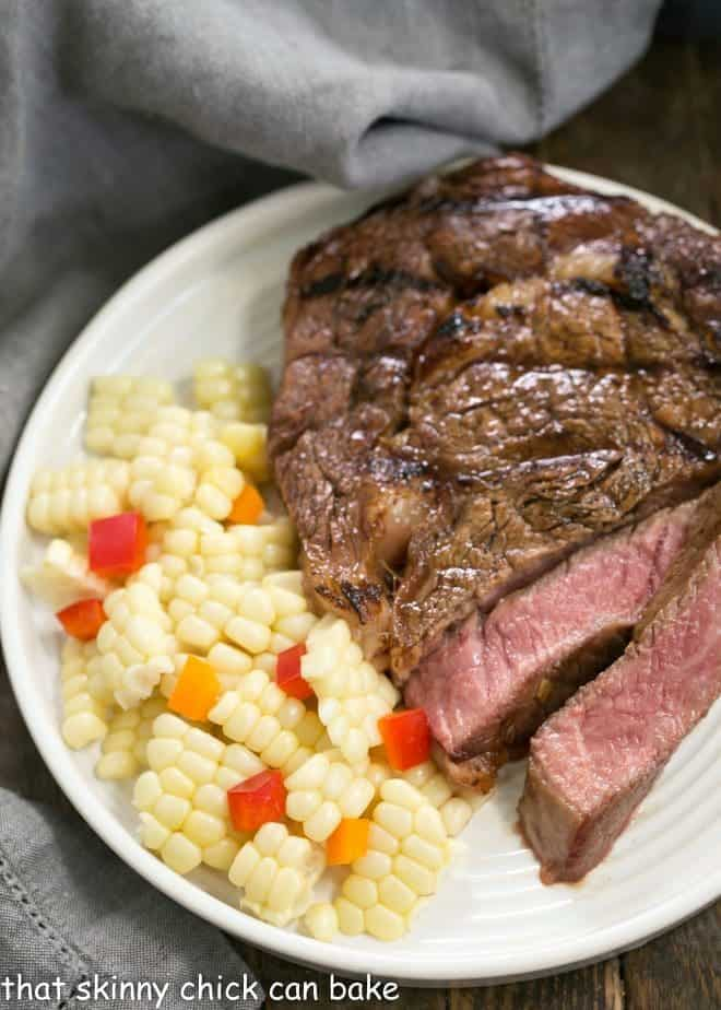 Grilled Korean Beef Steaks sliced on a white plate with corn