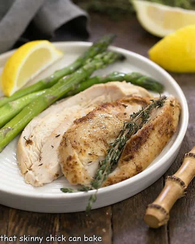 Instant Pot Rotisserie Chicken sliced with asparagus on a white dinner plate