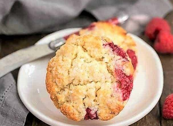 raspberry cream scones on a round white plate with a red handled knife