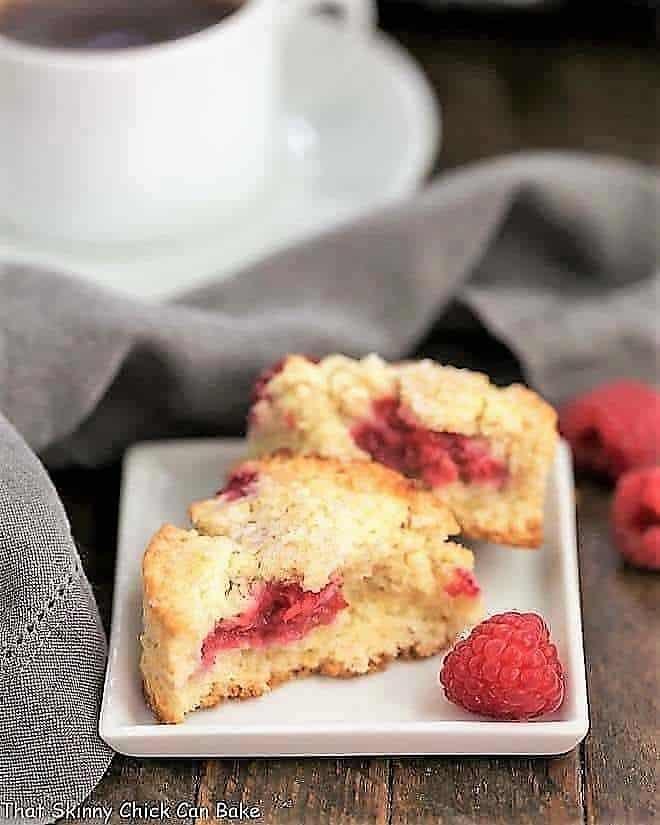 Raspberry Cream Scones broken in half on a white plate with a raspberry garnish