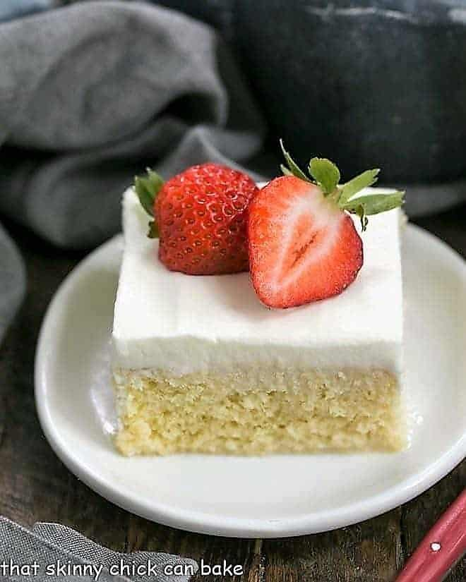 Authentic Tres Leches Cake slice topped with strawberry halves on a white plate