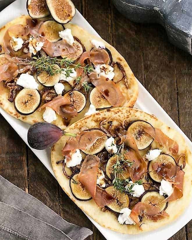 Fig, Goat Cheese and Prosciutto Pizza on a white platter with fresh figs