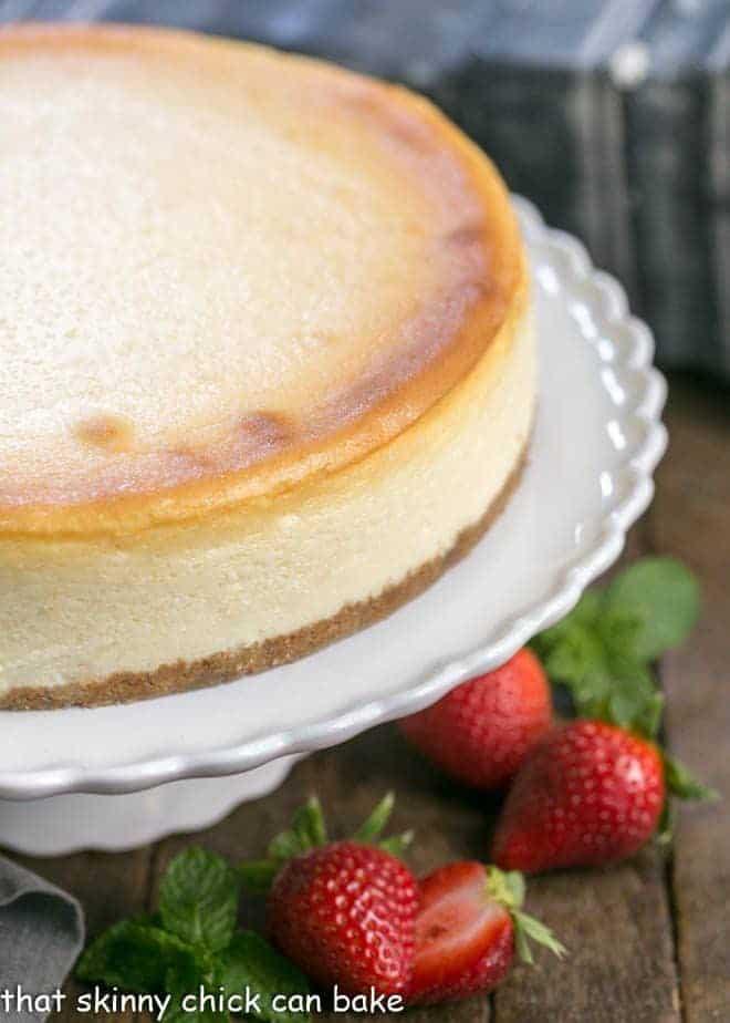 Perfect vanilla cheesecake on a white ceramic cake stand
