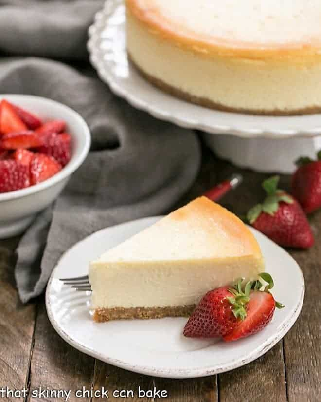 A slice of perfect vanilla cheesecake with a strawberry garnish