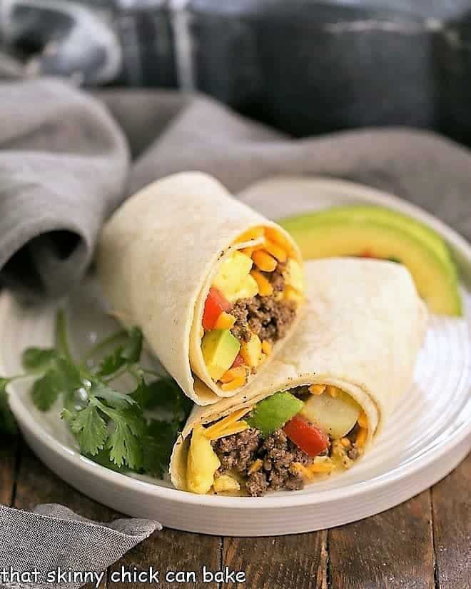 Tex-Mex Breakfast Burritos on a white plate with cilantro and avocados