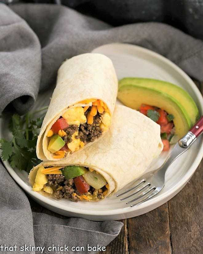 Tex-Mex Breakfast Burritos cut in half on a round white plate