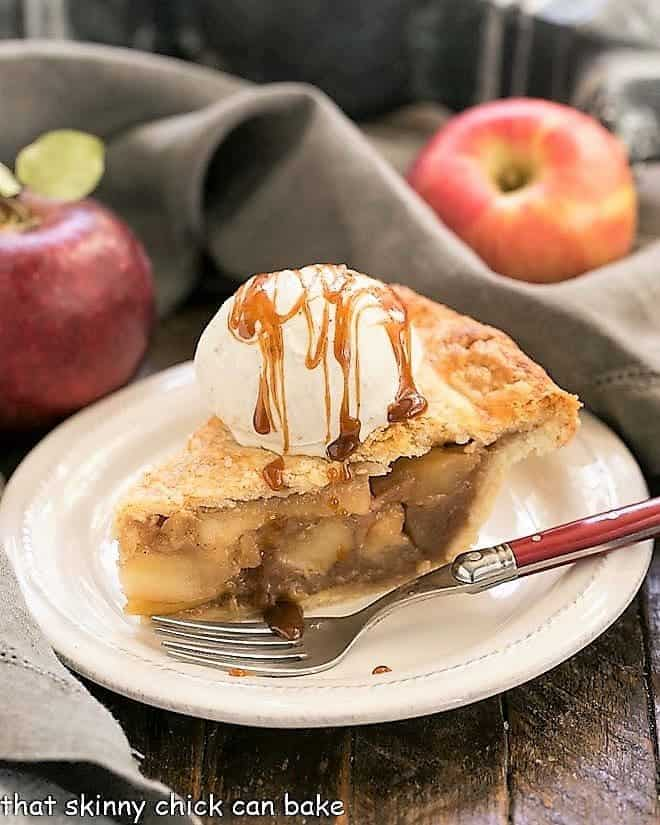 Slice of Caramel Apple Pie on a white plate with a red handled fork
