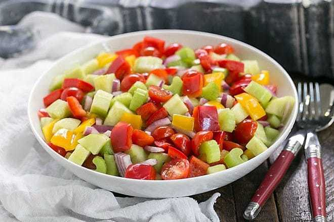 Marinated Vegetable Salad in a white serving bowl with red handled serving spoon and fork