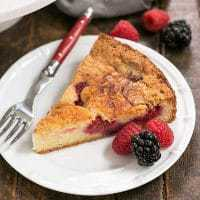 Mixed Berry Torte on a dessert plate with a fork and berries