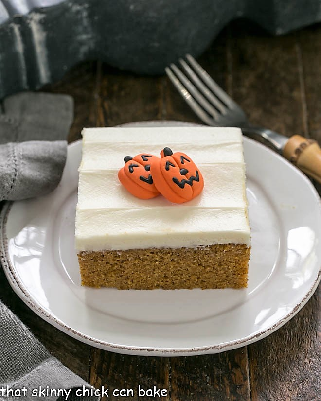 A pumpkin bar on a round white plate with 2 mini pumpkin candies to garnish