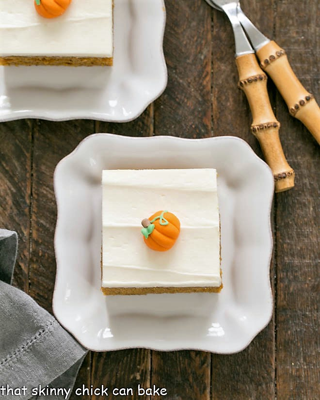 Overhead view of 2 Killer Pumpkin Bars with Cream Cheese Frosting on square white plates