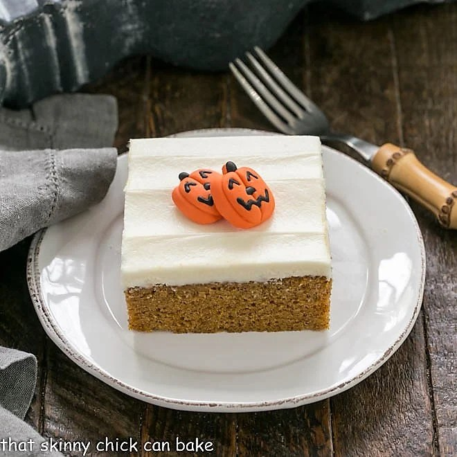 One pumpkin bar garnished with 2 candy pumpkins on a round white plate