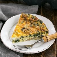 Slice of Crustless Spinach Quiche on a white plate with a bamboo handled fork