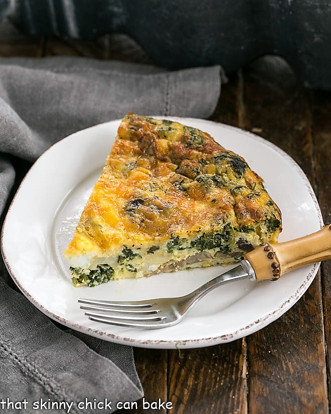 Slice of spinach quiche on a round white plate