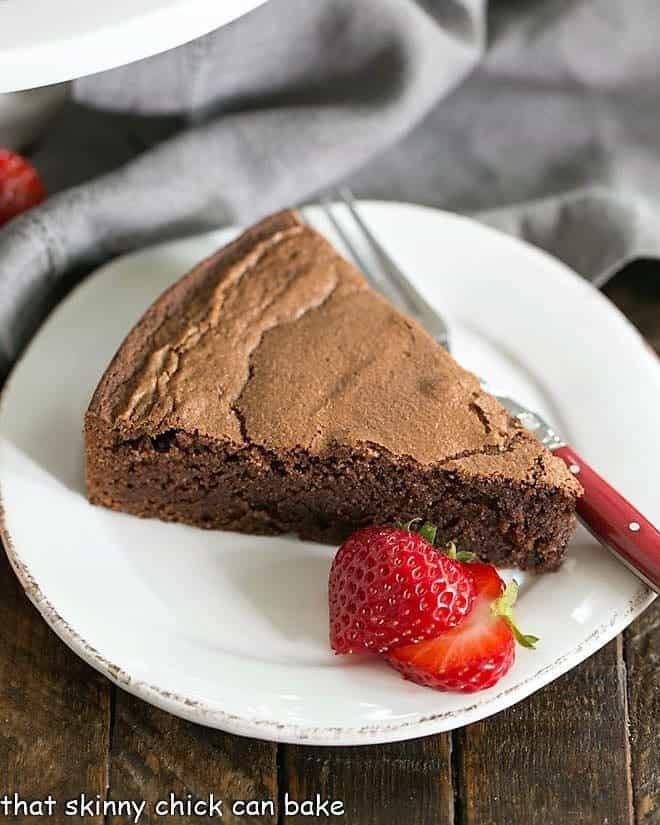 Italian Flourless Chocolate Cake on a white plate with strawberries