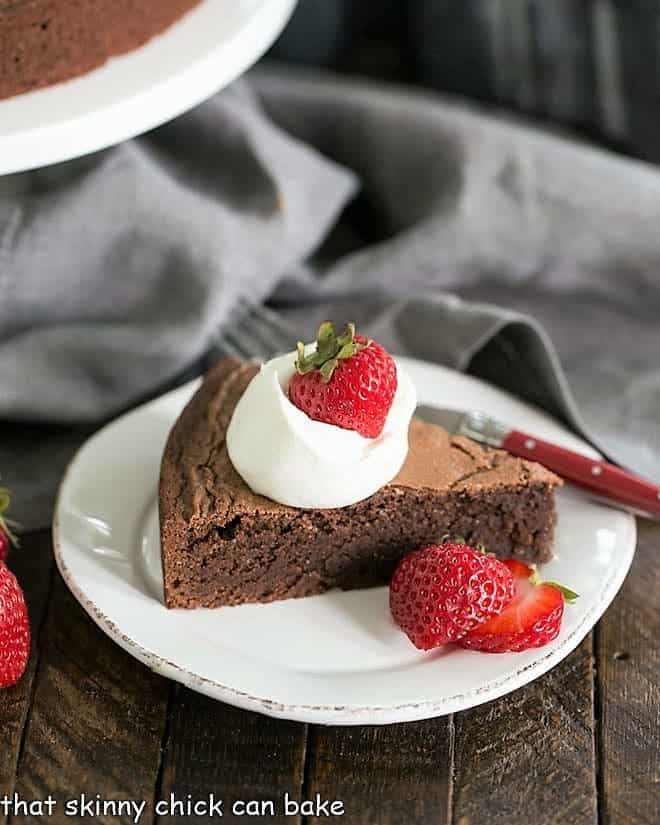 Italian Flourless Chocolate Cake on a white dessert plate with a dollop of cream and strawberries