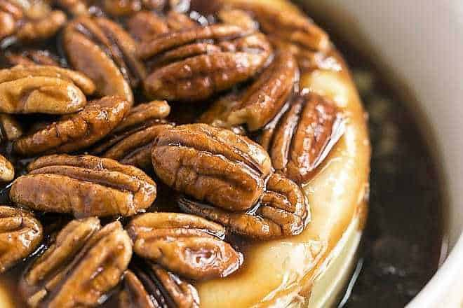 Kahlua Caramel Baked Brie in a round ceramic baking dish topped with pecans