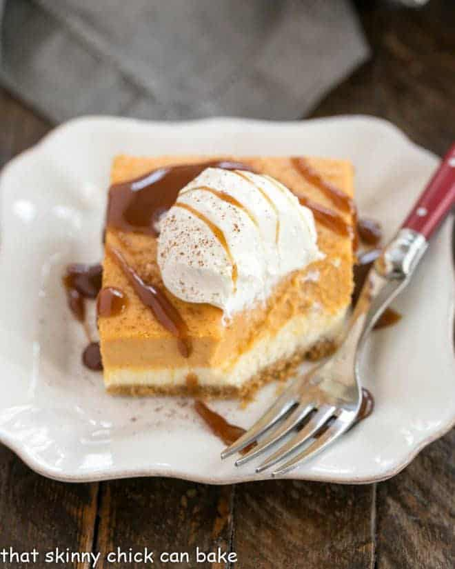 A slice of layered pumpkin cheesecake bars on a square dessert plate with a red handled fortk