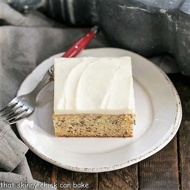 Sour Cream Banana Cake on a round white plate with a red handled fork