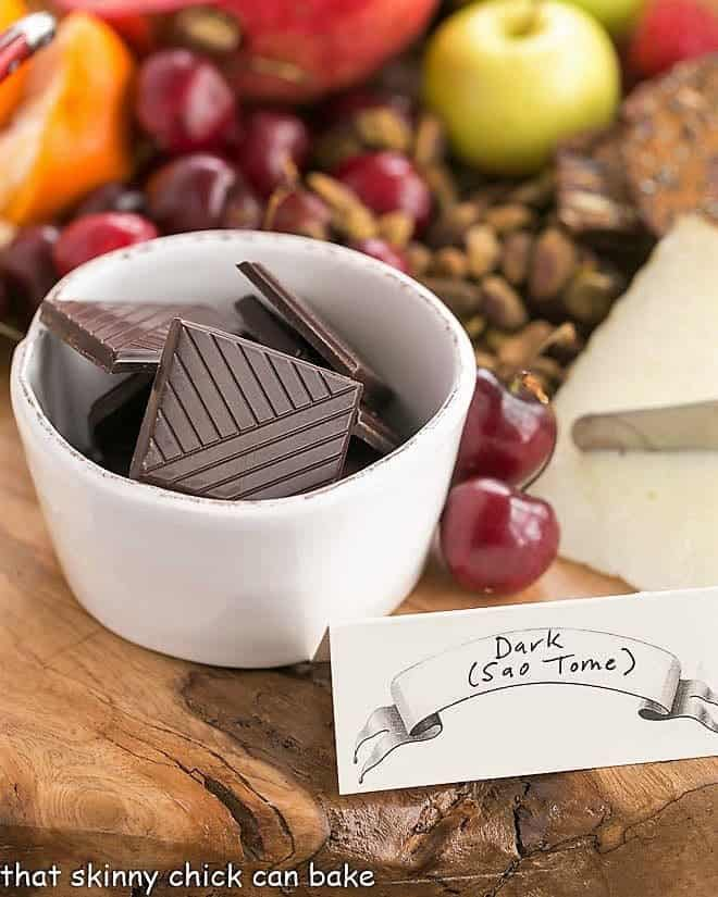 Chocolate squares in a white bowl with cherries and pistachios