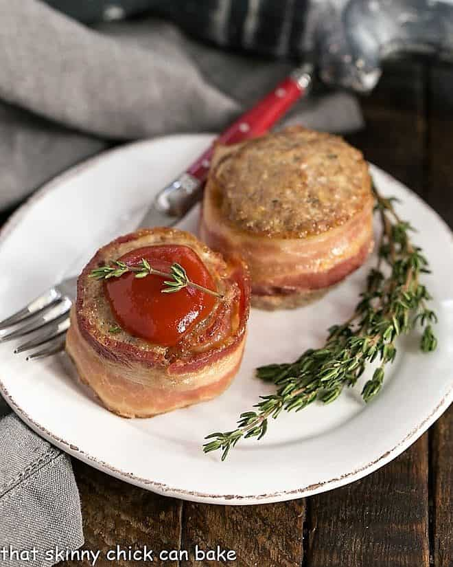 Two bacon wrapped meatloaf muffins on a round white plate
