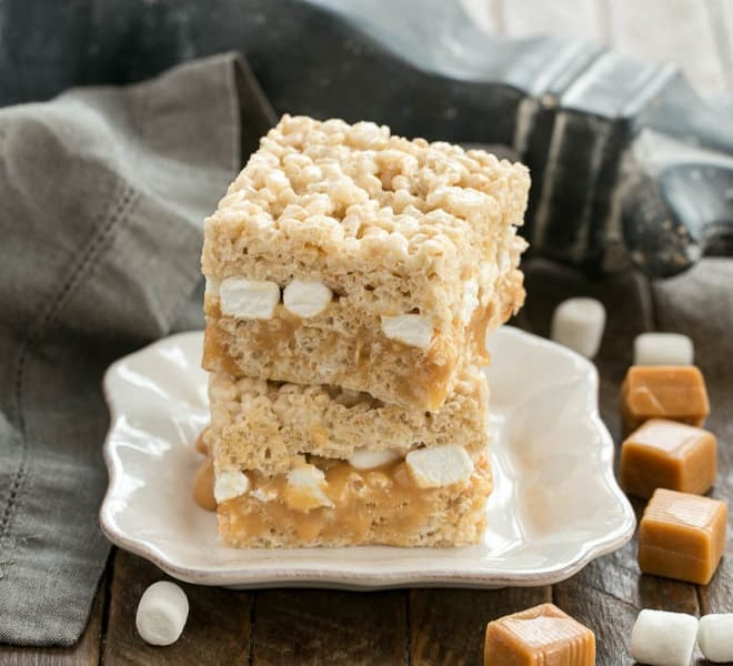 Caramel Stuffed Rice Krispie Treats stacked on a square plate