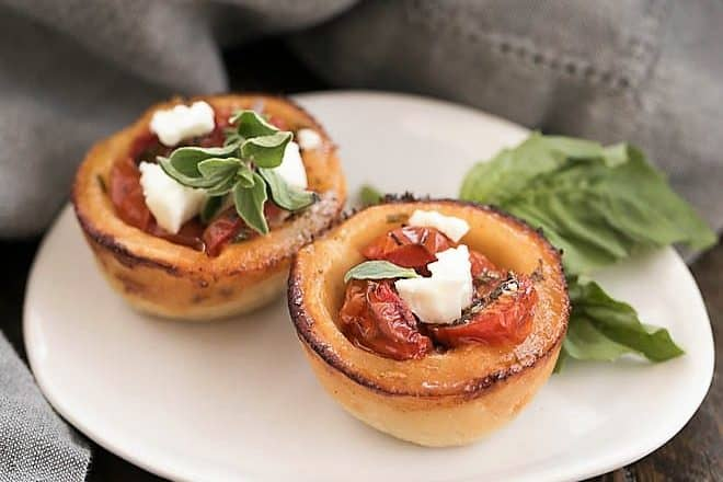 Cheese Straw Tomato Tartlets on an oval white plate with a sprig of basil