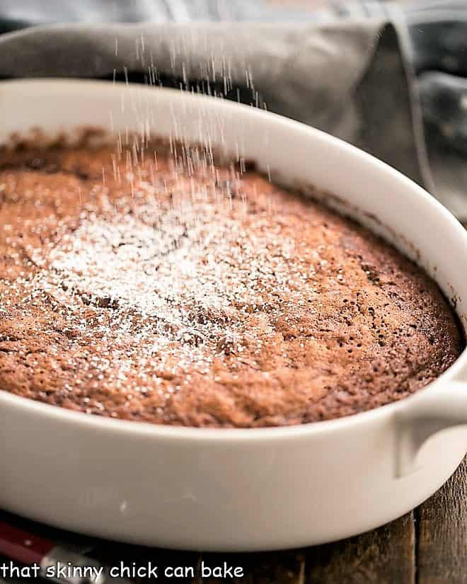 Self saucing chocolate pudding cake in an oval casserole dish dusted with powdered sugar