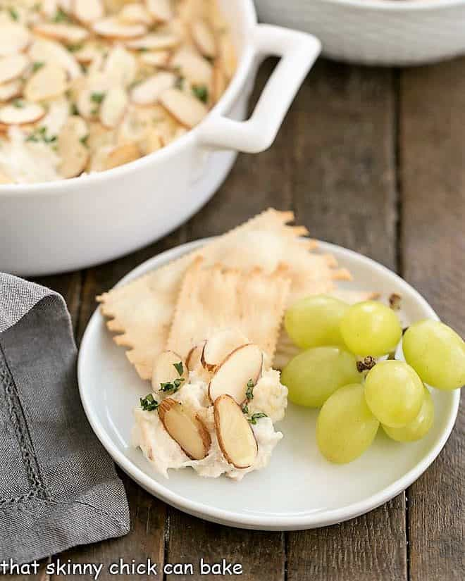 Parmesan Crab dip on an appetizer plate with crackers and green grapes