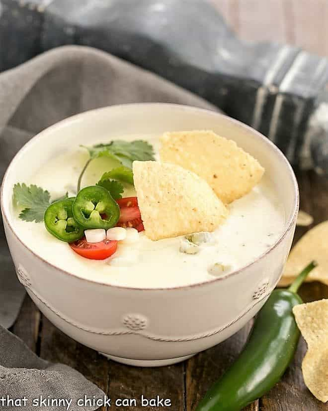 Easy Homemade Queso Dip in a white serving bowl topped with tortilla chips, jalapeno slices, cilantro sprig