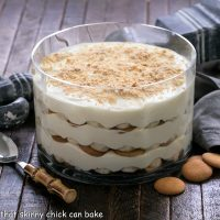 Banana pudding in a glass dish with a serving spoon and vanilla wafer cookies