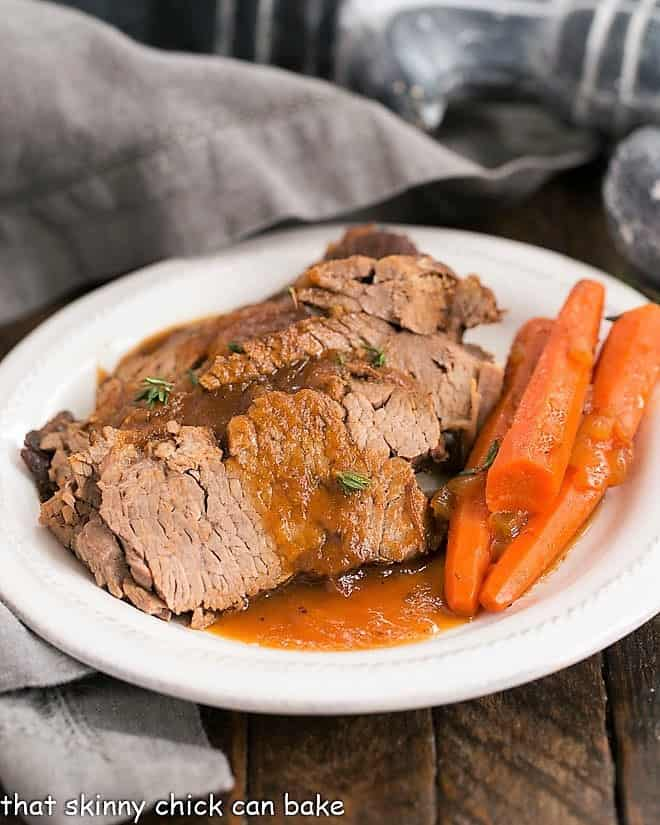 Braised Cola Brisket with Bourbon Gravy on a white dinner plate with carrots