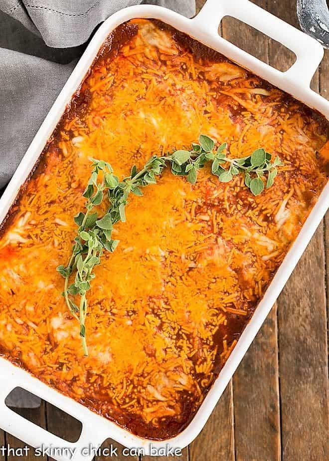 Turkey Enchilada Casserole in a white casserole dish with a sprig of oregano