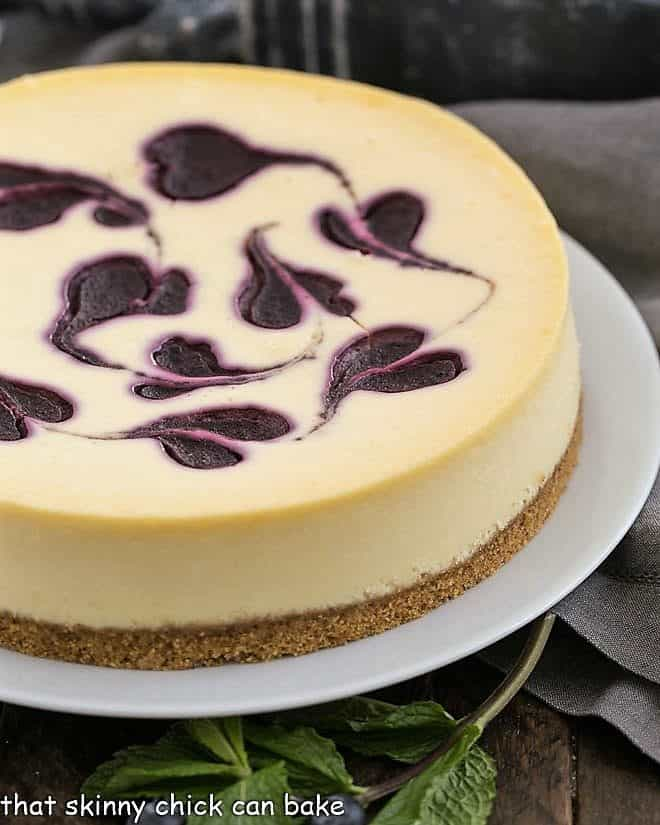 Uncut Blueberry Swirl Cheesecake on a white serving plate