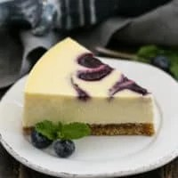 Blueberry Swirl Cheesecake slice on a white dessert plate