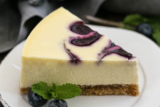 Blueberry Swirl Cheesecake slice on a white dessert plate