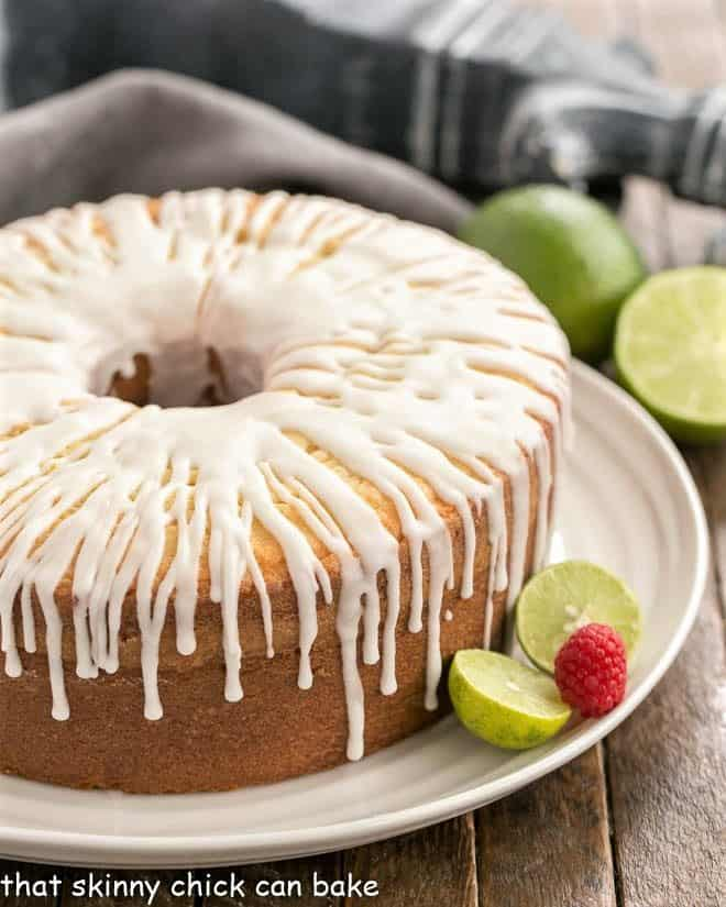 A close up of key lime pound cake on a white serving plate garnished with limes and a raspberry