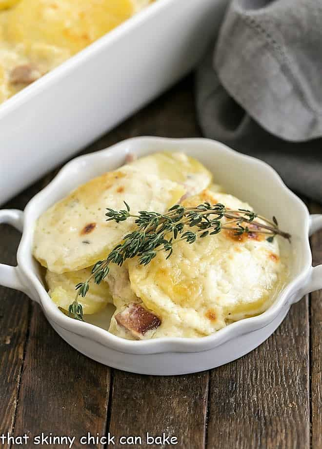 Best Scalloped Potatoes in a white dish topped with a thyme sprig