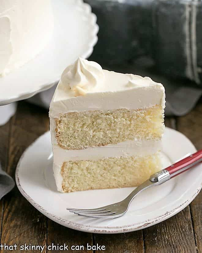 Slice of Classic White Layer Cake with White Chocolate Swiss Meringue Buttercream on a white dessert plate