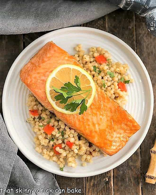 Easy Glazed Salmon overhead view on a white plate over couscous with a slice of lemon to garnish