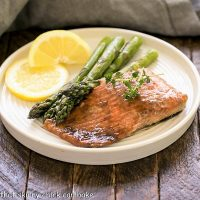 Easy Glazed Salmon on a white dinner plate with asparagus and lemons