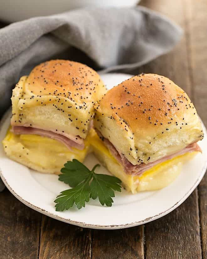 Ham, Egg and Cheese Breakfast Sliders on a small white plate with a sprig of parsley